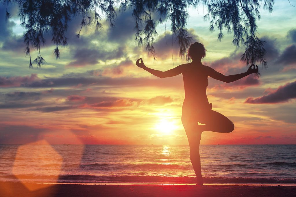 Young woman standing in yoga pose on the beach during the amazing sunset.